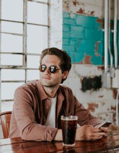 Junger Mann am Tisch trinkt Cola